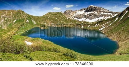 Remote Schrecksee lake up high in the alpine mountains in spring or summer. Bavaria, Allgau, Germany.