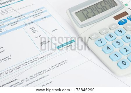 Close Up Studio Shot Of Unpaid Utility Bill And Calculator Over It