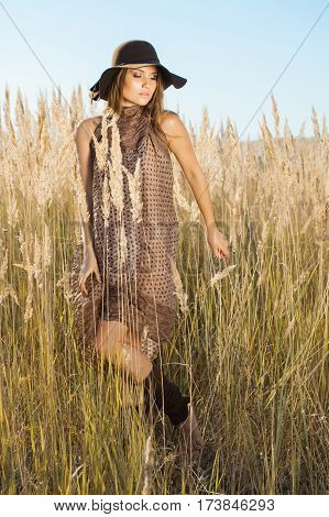 Model in hat walking through tallgrass - outdoors shot