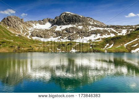 Beautiful reflections in the remote Schrecksee lake up high in the alpine mountains spotted with snow in spring or summer. Bavaria, Allgau, Germany.