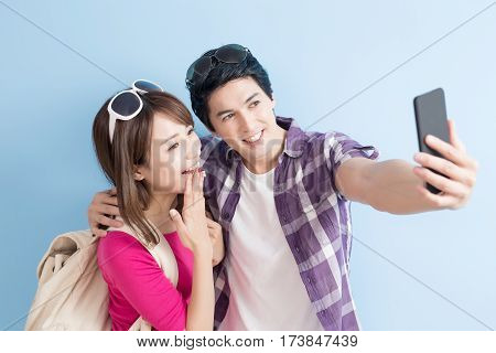 young couple selfie happily with blue background