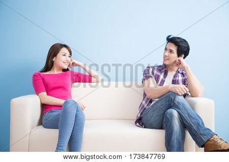 young couple look somewhere with blue background