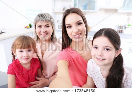 Mother, granny and girls taking selfie at kitchen