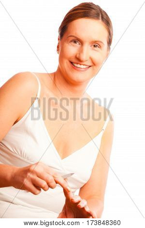 portrait of a woman in her forties filing her fingernails