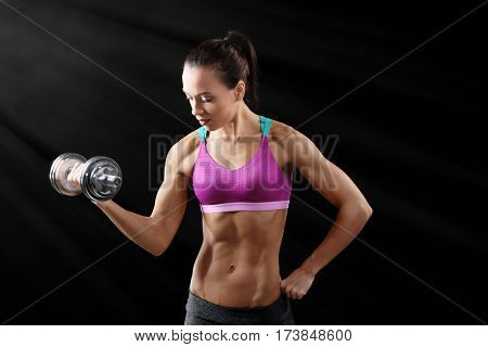 Sporty young woman with dumbbell on black background