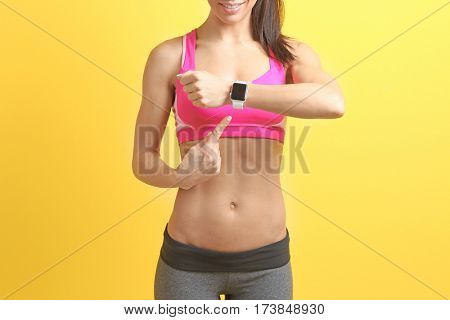 Young woman with fitness tracker on color background