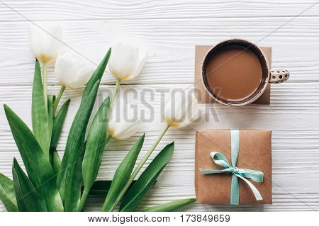 Stylish Craft Present With Morning Coffee And Tulips On White Wooden Rustic Background. Flat Lay Wit