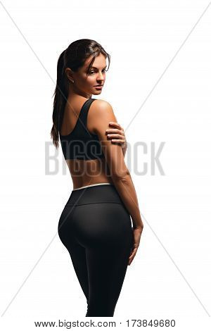 Sexy gentle athletic woman posing on a white background standing back in a half turn and look to the side. Beautiful figure of a young beautiful female athletes.