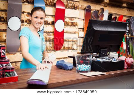 salesperson standing at cash register in ski store