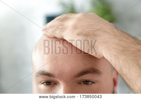 Bald adult man on blurred background, closeup