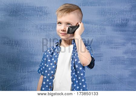 Cute little boy talking by telephone on color background