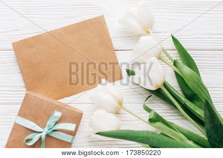 Stylish Craft Present With Greeting Card And Tulips On White Wooden Rustic Background. Flat Lay With