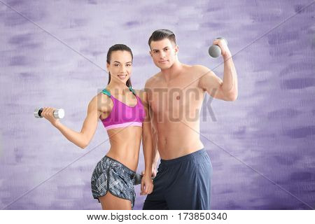 Young sporty couple with dumbbells in gym