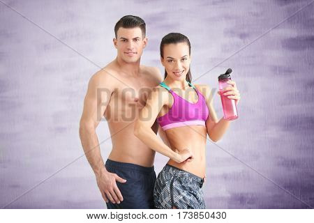 Young sporty couple with bottle of water in gym