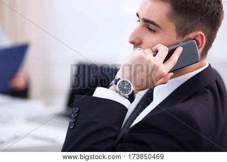 Business people talking on phone at office, sitting at the desk
