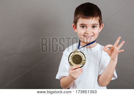 Happy little boy with golden medal standing and showing ok sign