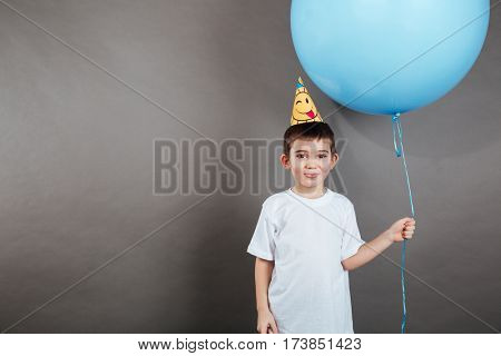 Funny little boy in birthday hat showing tongue and holding blue balloon