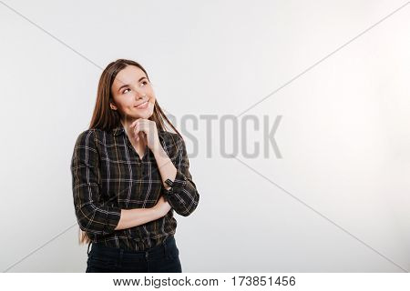 Smiling pensive Woman in shirt looking up. Isolated gray background