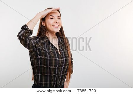 Smiling Woman in shirt looking away with hand on forehead. Isolated gray backgrlound