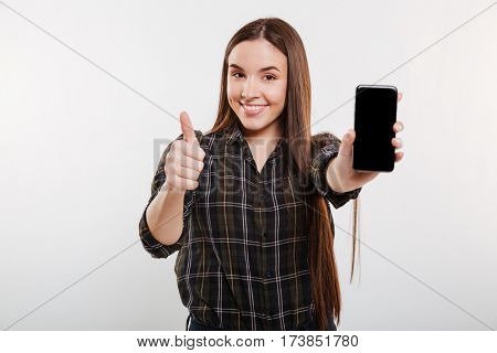 Smiling woman in shirt showing blank smartphone screen and showing thumb up. Isolated gray background
