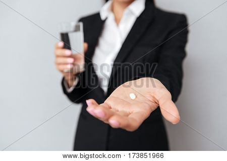 Cropped image of Business woman in suit and showing pill on the pound with cup of water on the second hand. Focus on the pound. Isolated gray background