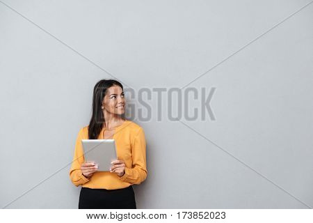 Business woman in suit which holding tablet computer and looking away. Isolated gray background