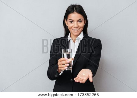 Portrait of a happy healthy business woman showing pill on her palm and holding glass of water isolated over gray background