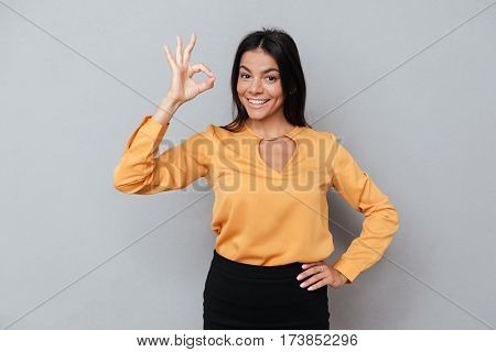Portrait of a happy smiling business woman showing okay gesture and looking at camera over gray background