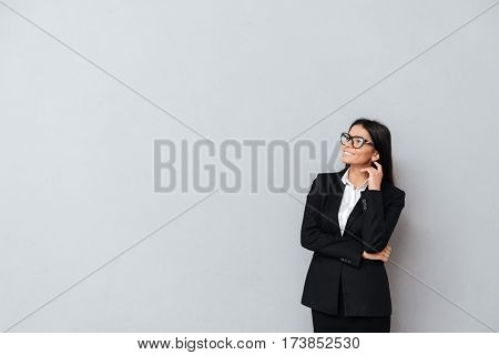 Portrait of a smart young business woman in eyeglasses thinking and looking away isolated on gray background