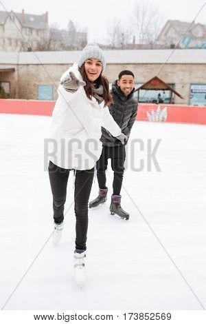 Happy multiethnic young couple skating and having fun at outdoor rink