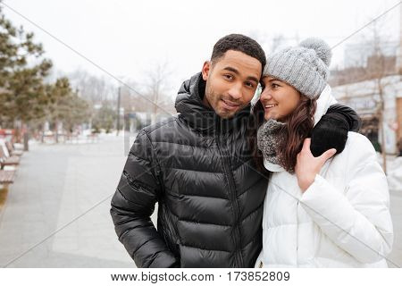 Happy multiethnic young couple standing and hugging in winter park