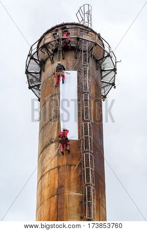 Large view on the workers climbing on the big chimney