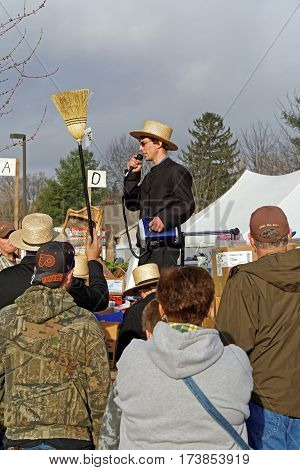 STRASBURG PENNSYLVANIA - February 25, 2017: Amish auctioneers volunteer at the annual Mud Sale to benefit the Fire Company. Sale items include quilts antiques crafts food sporting goods tools farm equipment and horses.