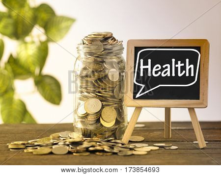 saving jar full of coins and mini blackboard with text health