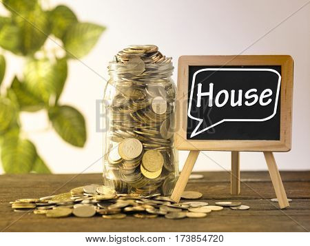 saving jar full of coins and mini blackboard with text house