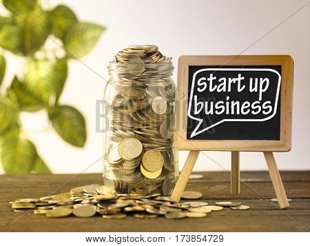 saving jar full of coins and mini blackboard with text start up business