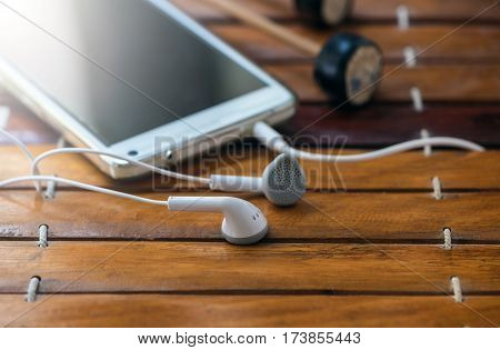 Smart phone and earphones on xylophone (Thai xylophone Musical Instruments) background