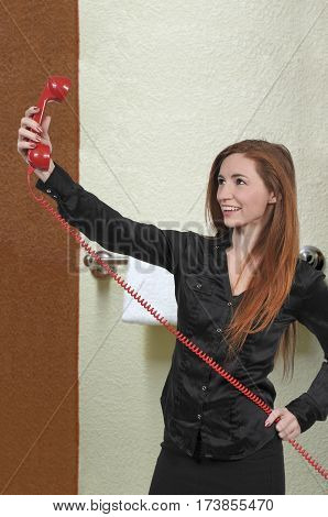Beautiful woman trying to take a selfie with a vintage rotary phone