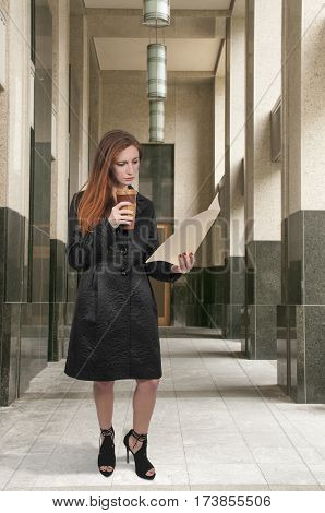 Beautiful young woman lawyer or business woman holding a manila file folder and to-go cup of coffee.