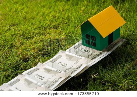 indian new currency notes of rupees 500 or 2000 forming a road to reach model house over green grass  - concept of residential property or home buying in india