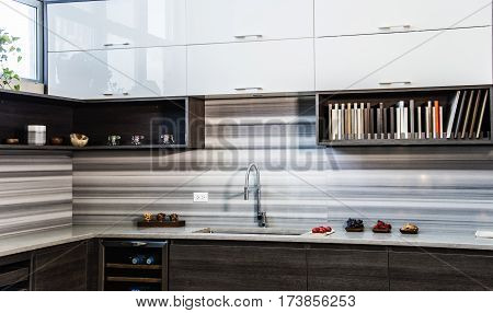 Perspective view of a modern kitchen, modern style of flat kitchen doors, brown slab cabinets of modern kitchen, granite counter tops and modern full backsplash