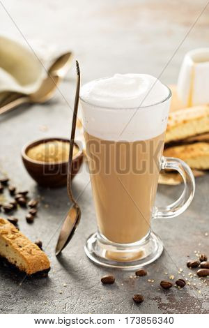 Hot coffee latte with brown sugar and biscotti cookies in tall glass