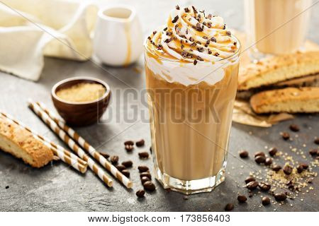 Iced caramel latte coffee in a tall glass with syrup and whipped cream