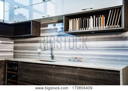 Small kitchen area with counter top and backsplash. Kitchen room has brown kitchen base cabinets and white kitchen wall cabinets, with book shelves and under cabinet lights, interior room design of modern kitchen