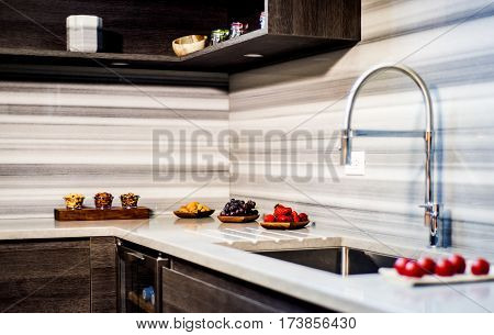 Kitchen counter. Kitchen granite counter with backsplash. Fruits on kitchen counter. Custom granite kitchen counter with stainless steel sink.
