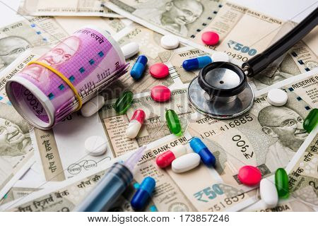 healthcare in india concept - showing indian new currency notes of rupees 500 and 2000 in the background with colourful pills, stethoscope, calculator, injection, fresh apple and blank card