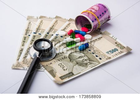 healthcare in india concept - showing indian new currency notes of rupees 500 and 2000 in the background with colourful pills, stethoscope,
