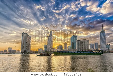 Ho Chi Minh City, Vietnam - February 14th, 2017: Riverside City sunset clouds in the sky at end of day brighter coal sparkling skyscrapers along beautiful river in Ho Chi Minh City, Vietnam