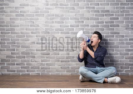 handsome man sit and take microphone with brick wall asian