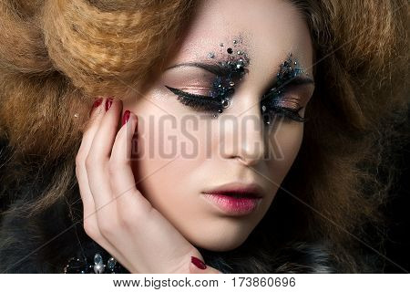 Beauty portrait of young woman with fashion makeup with rhinestones touching her face. Studio shot. Carnival or party makeup